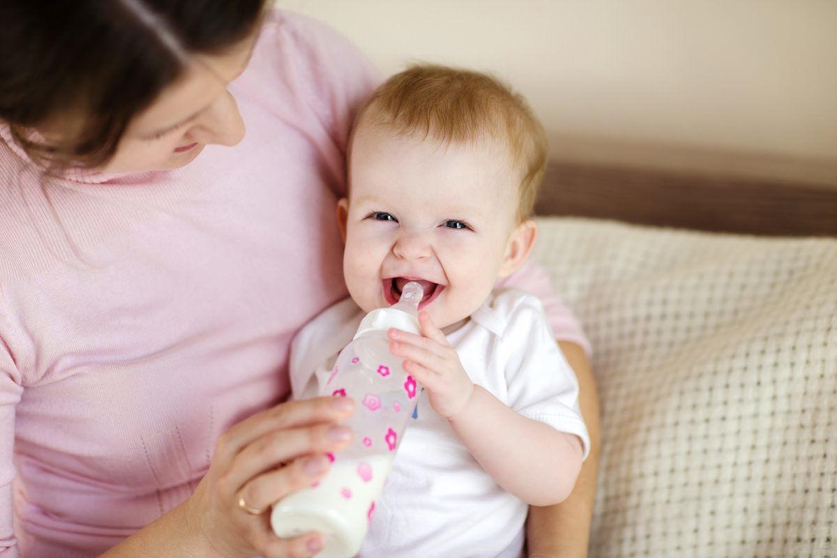 笑顔で哺乳瓶を飲む赤ちゃん