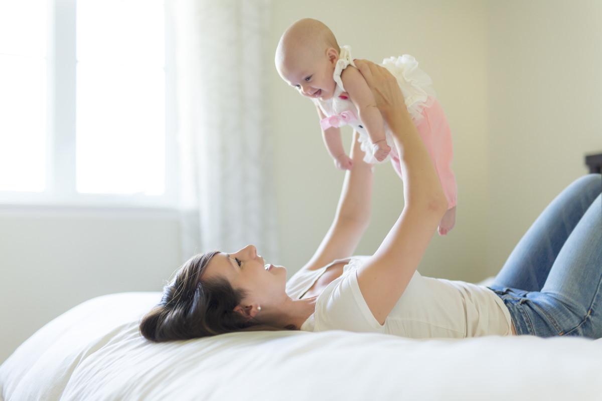 寝転がって赤ちゃんを抱き上げる母親