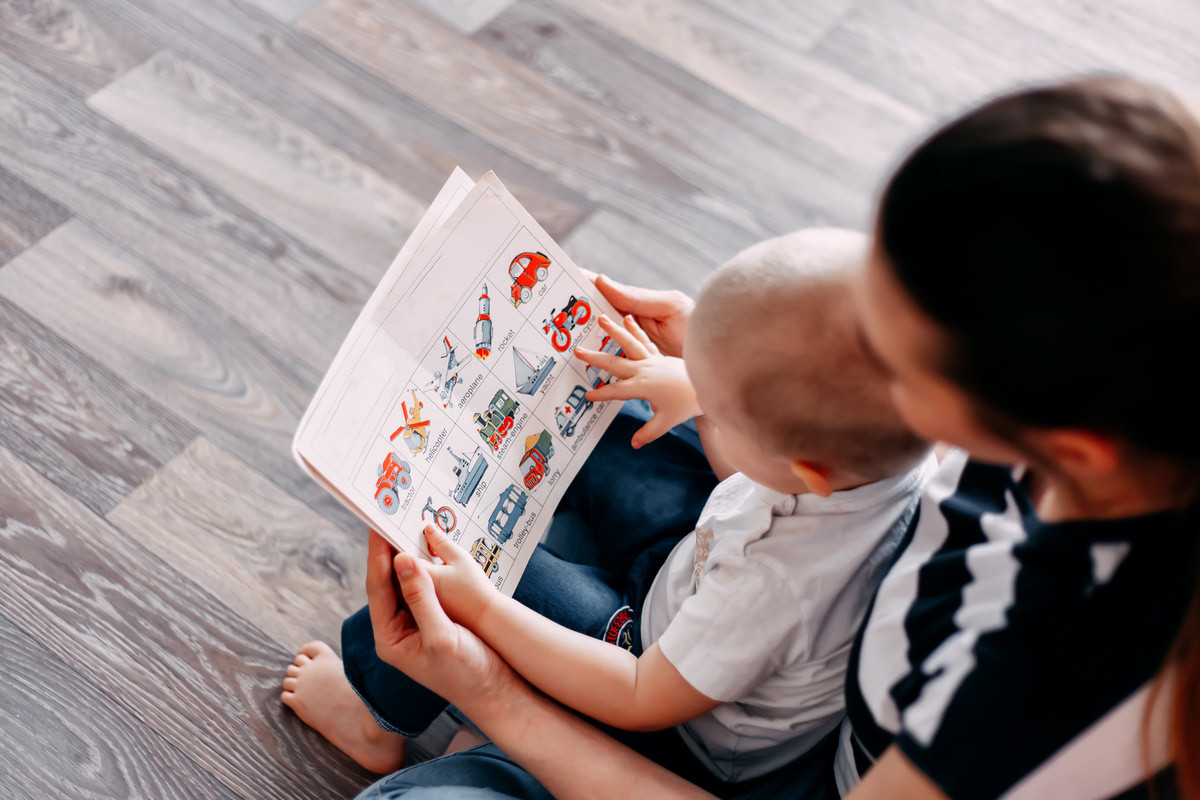 子供を膝の上に乗せて絵本を読む母親