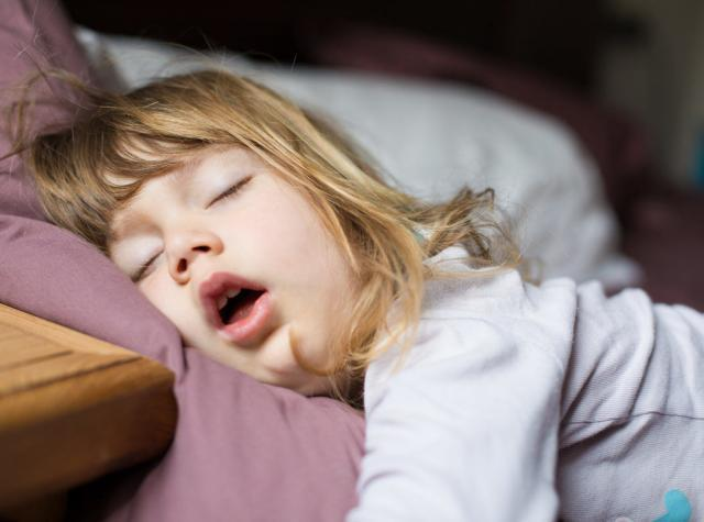 睡眠不足で口を開けて寝る少女