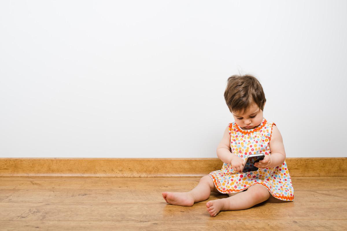 一人でスマホで遊ぶ赤ちゃんの画像