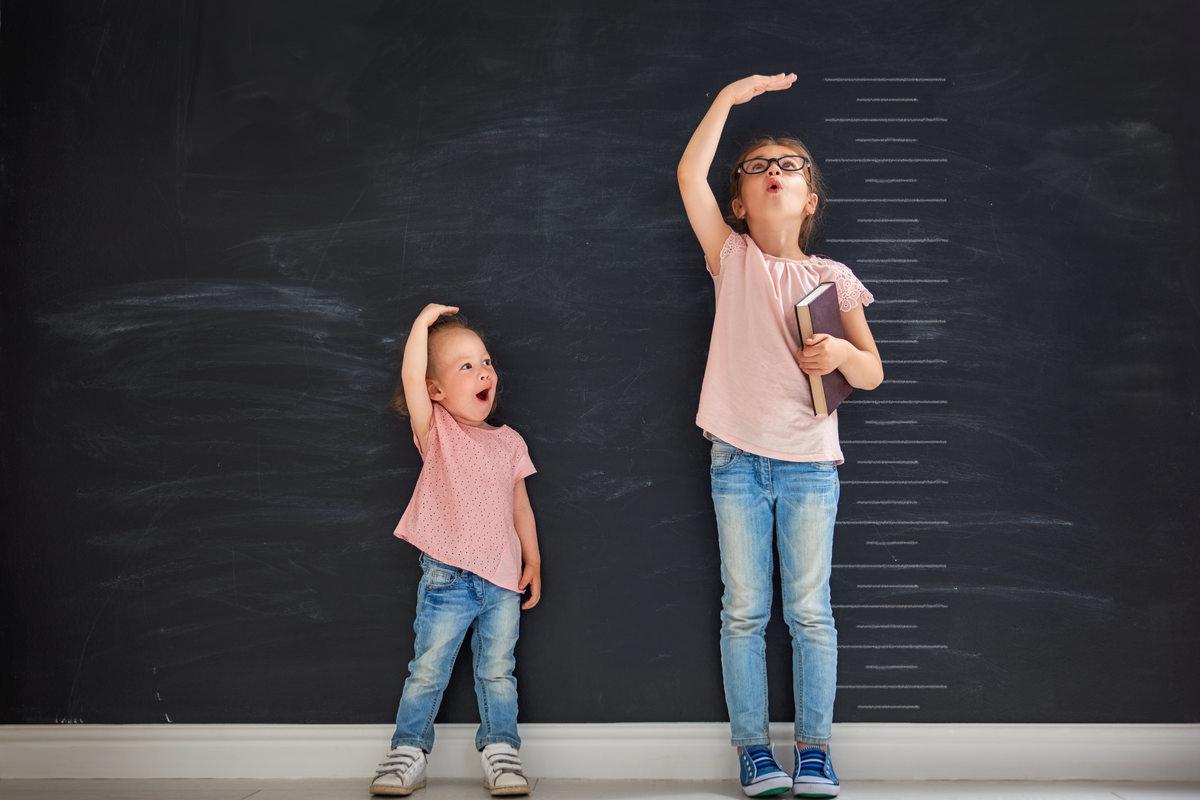 身長比べをしている二人の子供