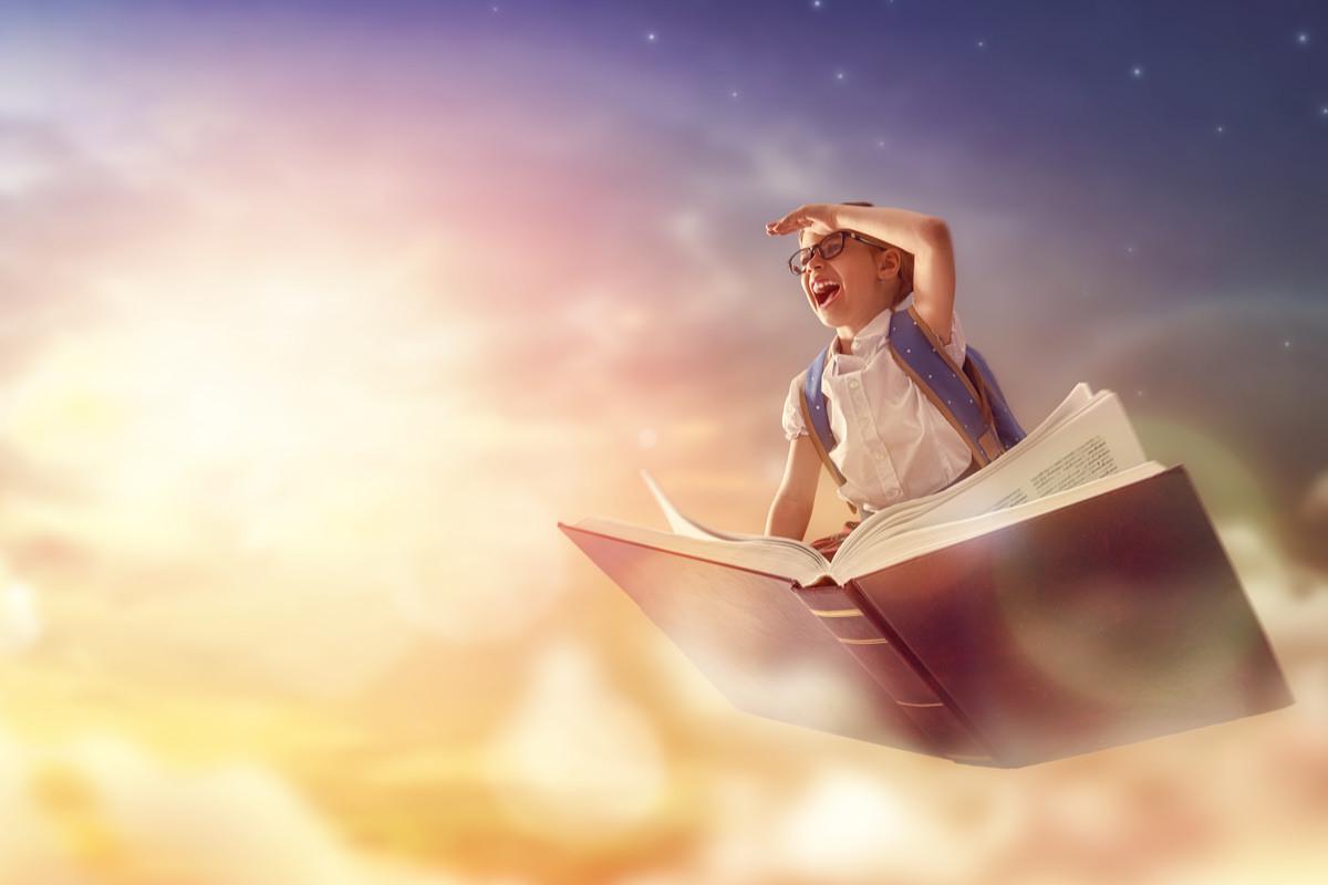 子供が空飛ぶ本に乗って冒険している画像