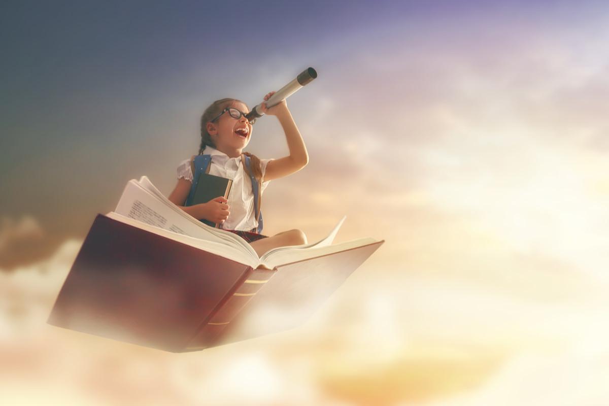 空飛ぶ本に乗る女の子