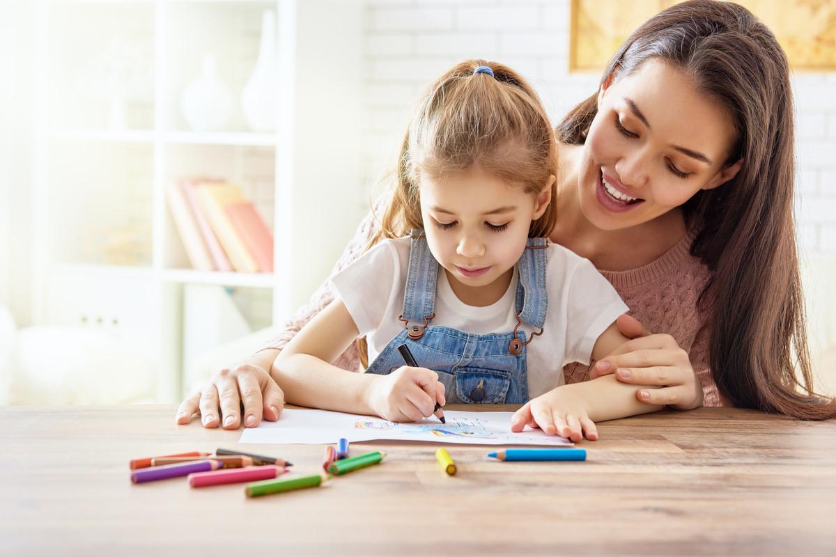 塗り絵をする子供と一緒に遊ぶ母親