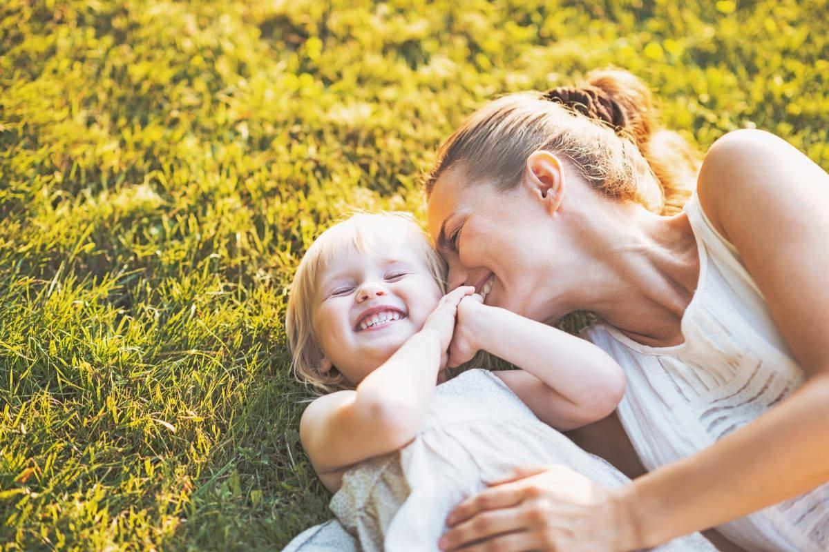 外で寝転び笑顔で抱き合う母親と子供