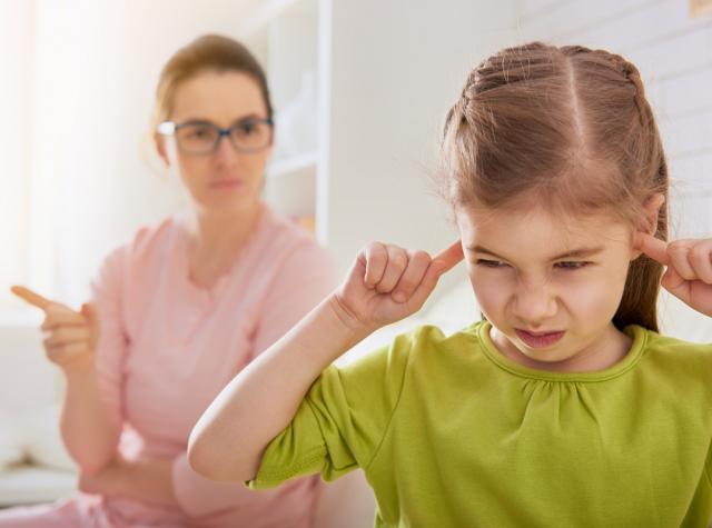 うるさくて耳を塞いでいる子供