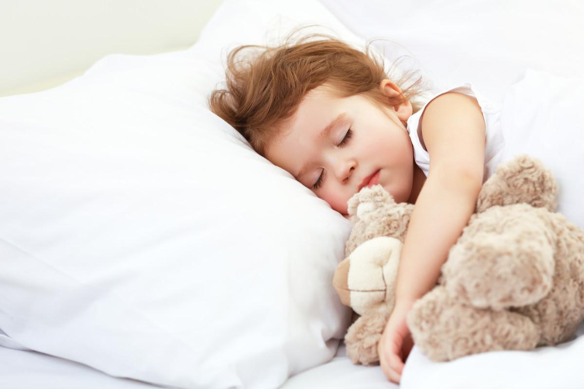 ぬいぐるみを抱えてすやすや眠る子供